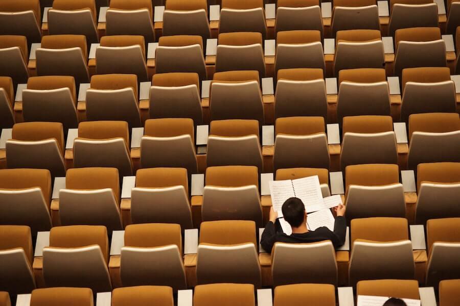 student reading notes in auditorium